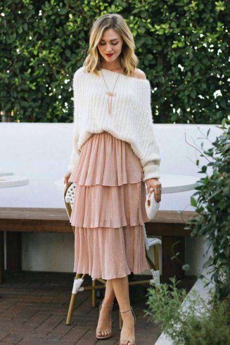 Chica rubia con suéter blanco y maxi falda rosa con olanes