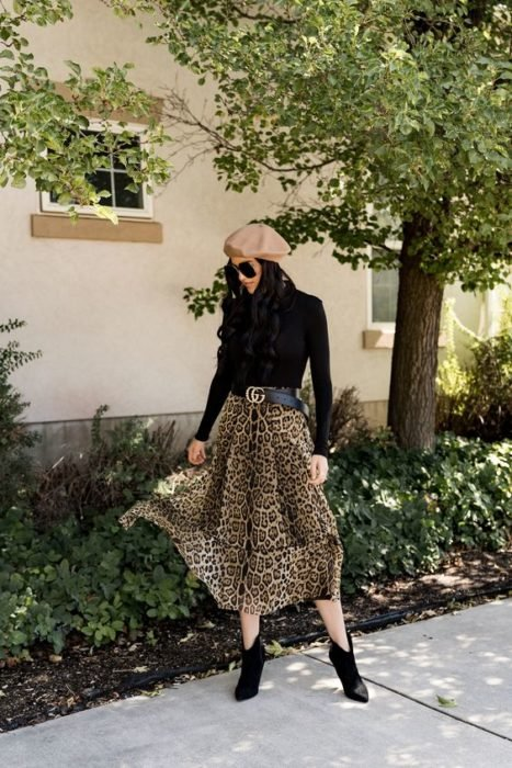 Girl posing with black long sleeve blouse, beige hat and leopard print maxi skirt
