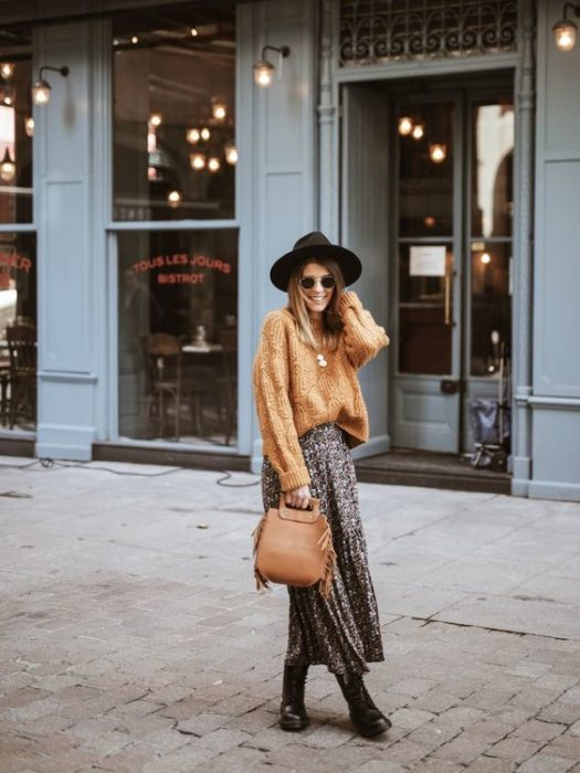 Brown-haired girl with black hat, long yellow sweater and animal print maxi skirt