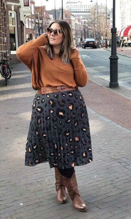 Plus size girl with orange sweater, gray maxi skirt with leopard spot and boots