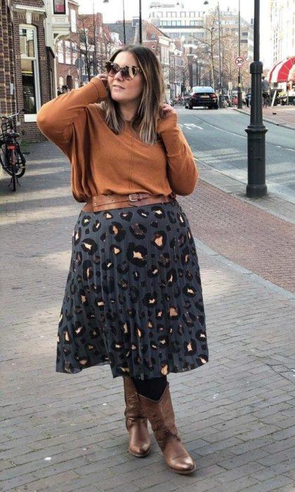 Chica plus size con suéter naranja, maxi falda gris con mancha de leopardo y botas