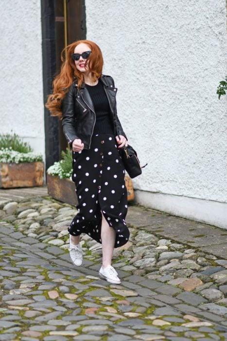 Chica pelirroja con blusa, chamarra y falda negras con tenia blancos
