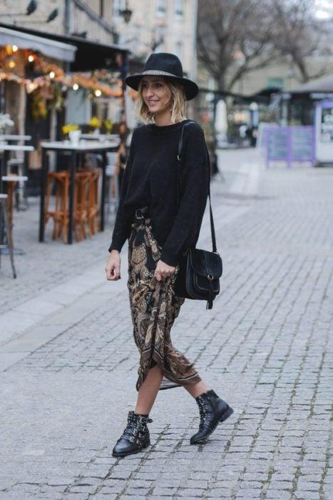 Chica rubia caminando en la calle con sombrero negro, suéter negros, botines negros y maxi falda de leopard print