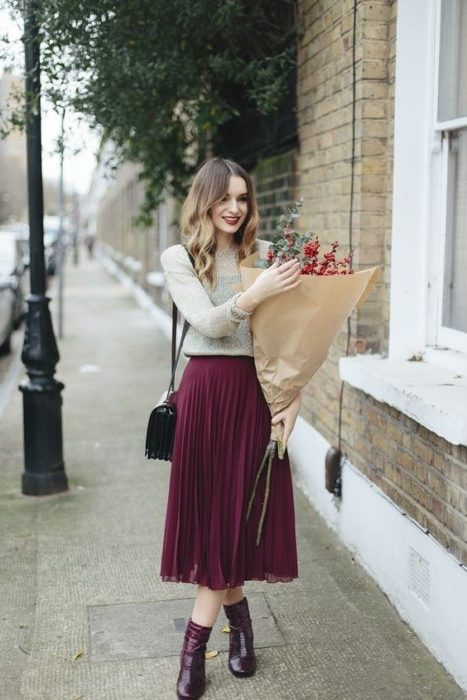 Slim girl with wavy brown hair in white turtleneck blouse with burgundy skirt and black ankle boots
