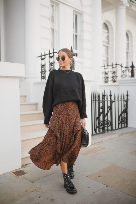 Blonde girl with combed hair in a bun, black sweatshirt and orange animal print maxi skirt