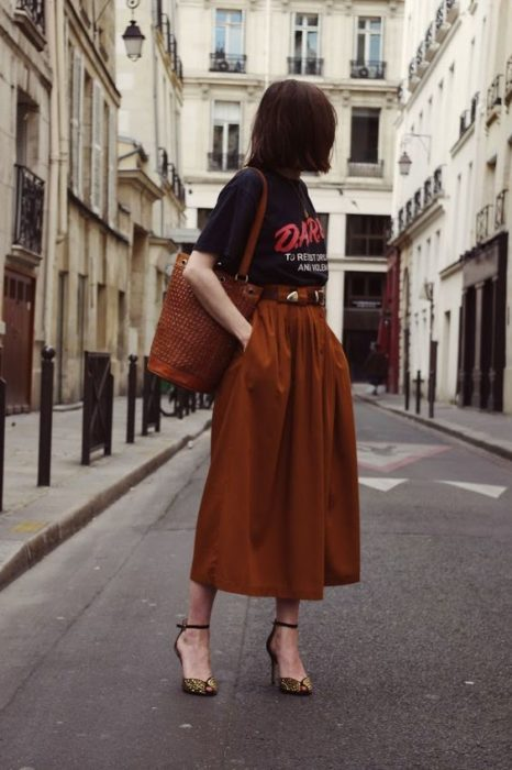 Girl posing in the street with black blouse and long orange skirt and brown heels