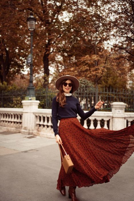 Long loose brown hair girl with sunglasses and hat with navy blue sweater and orange maxi skirt