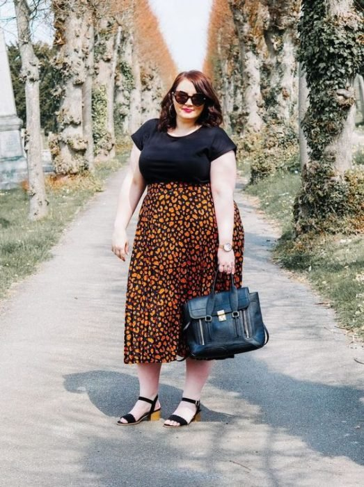 Redhead plus suze girl with black blouse and orange floral maxi skirts and black sandals