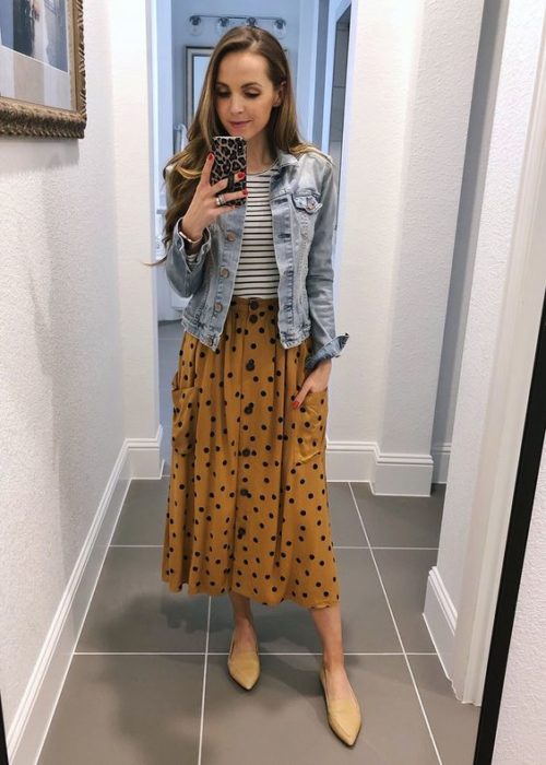 Girl taking selfie in front of mirror with yellow maxi skirt with black dots, white striped blouse with black and denim jacket