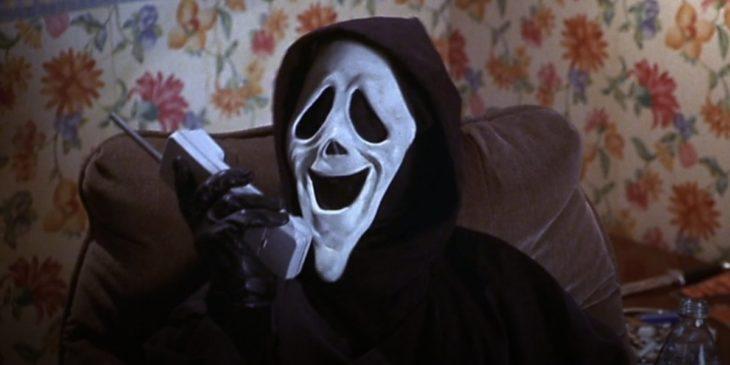 Escena de la película Scream. Hombre enmascarado contestando el teléfono