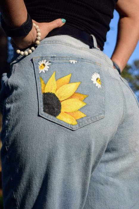 Chica llevando jeans con dibujo de girasol