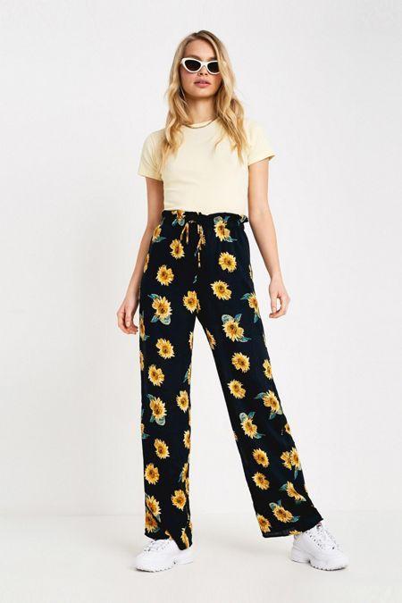 Chica llevando pantalones anchos en color negro con estampado de girasoles