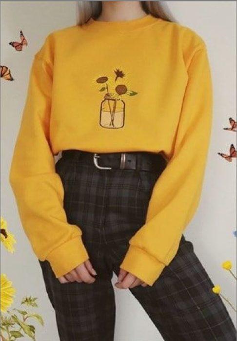 Chica lelvando sudadera amarilla con bordado de girasoles