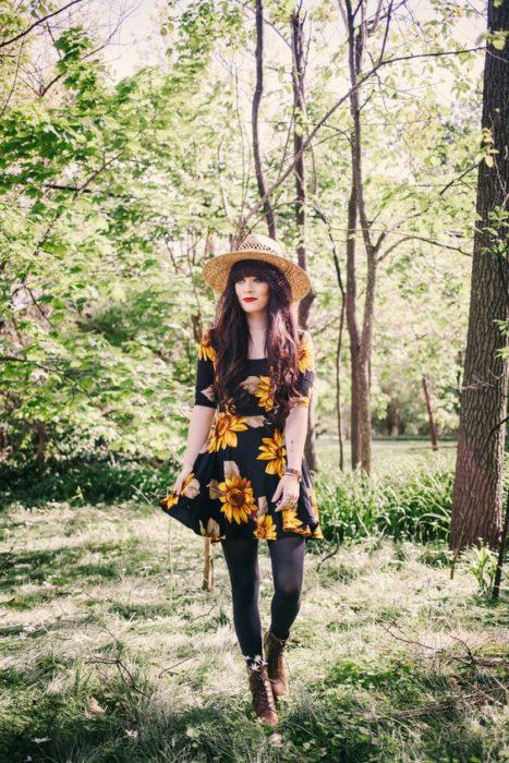 Chica llevando vestido negro con girasoles en estampado