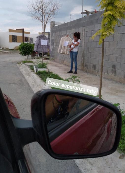 Chica en la calle intercambiando ropa por artículos para bebé