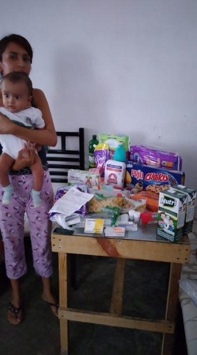 Chica sosteniendo a su bebé y agradeciendo por la despensa que le regalaron
