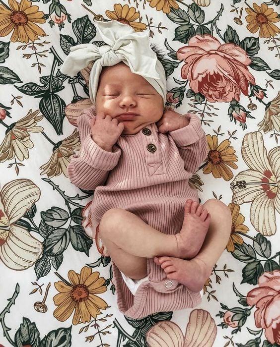 Bebé recién nacida con pañalero rosa y diadema blanca de moño