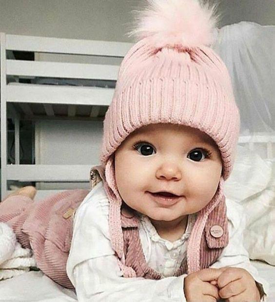 Bebé acostada boca abajo con gorro rosa