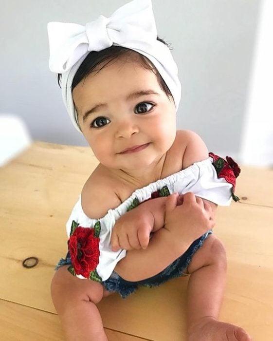 Bebé con diademas grande blanca con moño y blusita blanca con rosas rojas