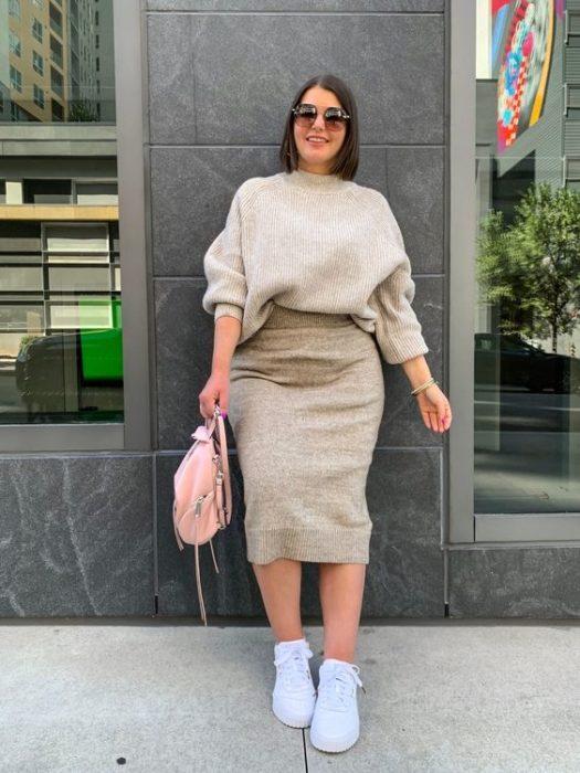 Chica curvy usando tenis blancos, falda lapiz y suéter color arena