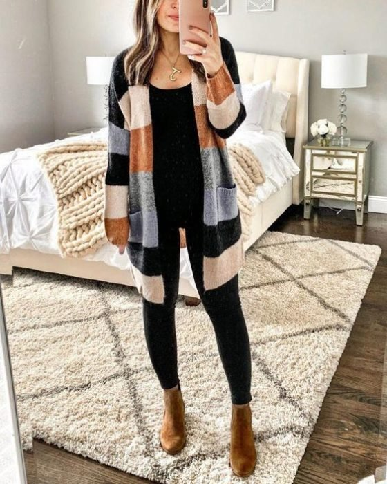 Girl wearing black jeans, black top, camel ankle boots and long striped sweater of different colors