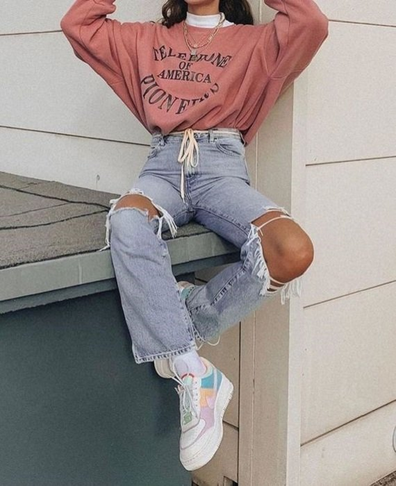 Girl wearing ripped mom jeans, tennis shoes, and white turtleneck blouse with pale pink oversized sweatshirt