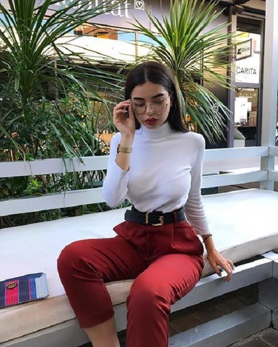 Girl wearing red high-waisted pants, with black belt, and white, long-sleeved, high-neck blouse