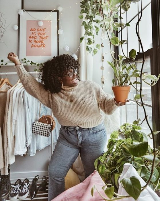 Curvy girl wearing faded jeans with beige knit sweater