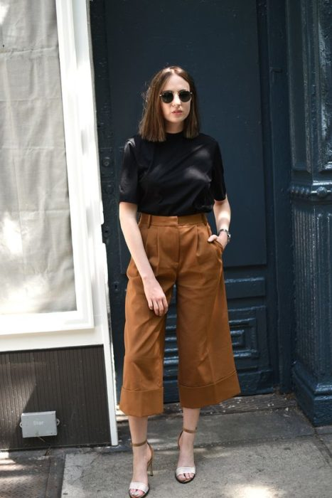Girl wearing camel flared pants, black blouse and heels