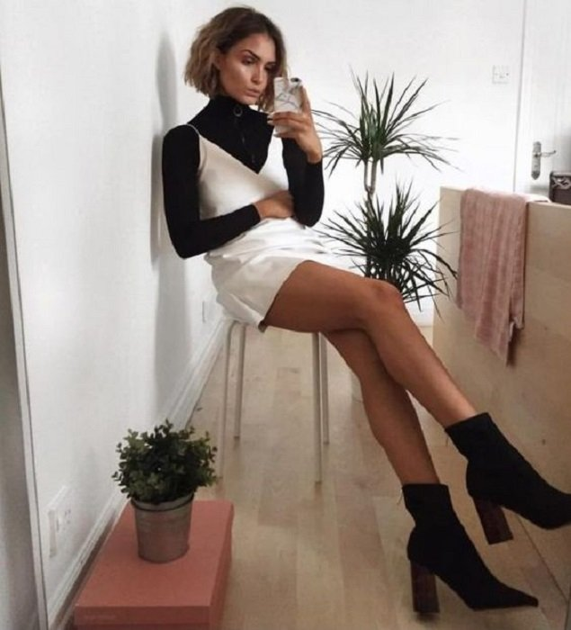 Girl wearing pearl-colored silk strap dress, with black blouse underneath and black high-heeled ankle boots