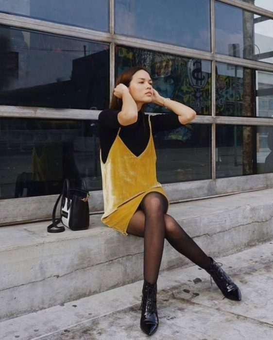 Girl wearing short mustard-colored strapless dress, with a three-quarter sleeve blouse and black high neck, and black stockings and ankle boots of the same color