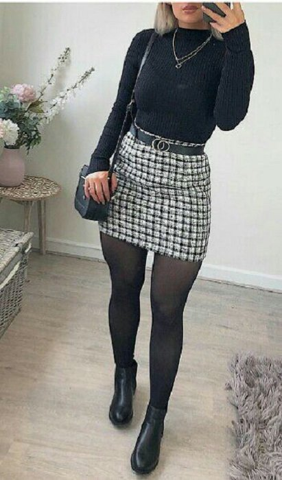 Girl wearing black stockings, ankle boots and long-sleeved, high-neck blouse with a black and white tartan print skirt with belt