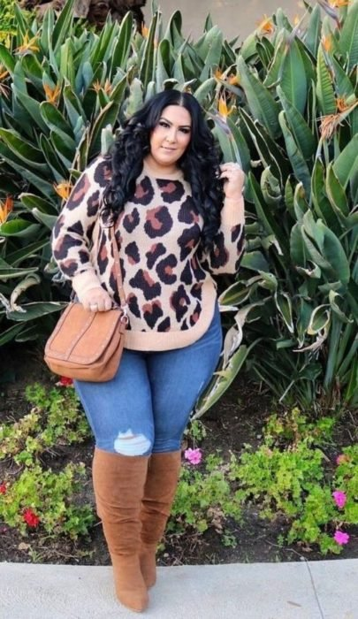 Curvy girl wearing knee high boots and camel bag, denim jeans and animal print sweater