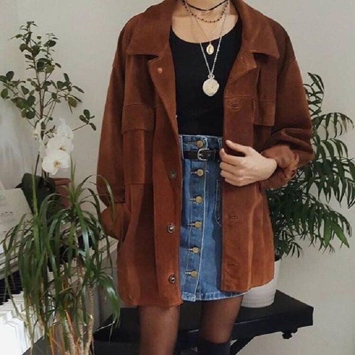 Girl wearing black tights, denim mini skirt, black top and oversized camel shirt