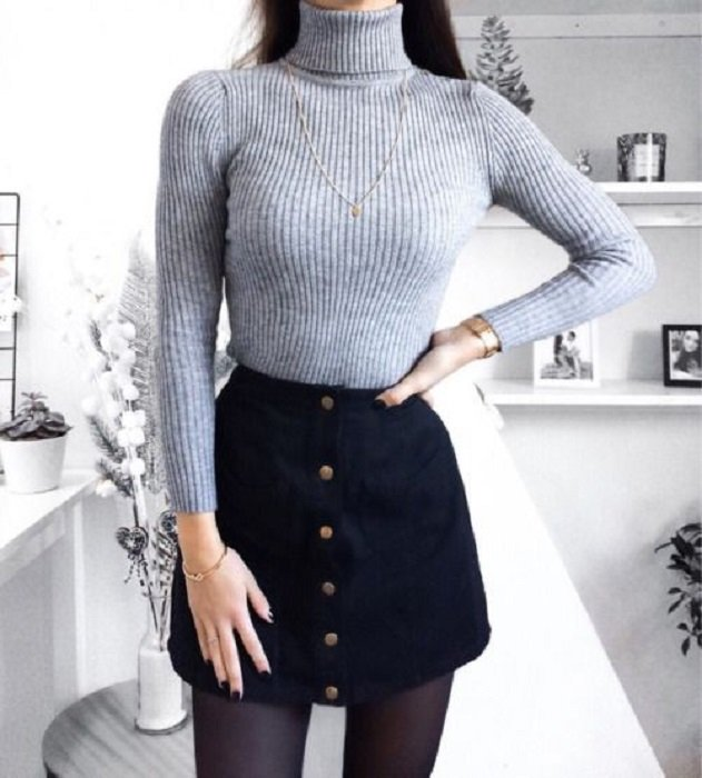 Girl wearing black tights and miniskirt, and gray-blue sweater with high neck and long sleeves