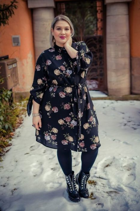 Curvy girl wearing black tights and ankle boots with flower print black long sleeve dress