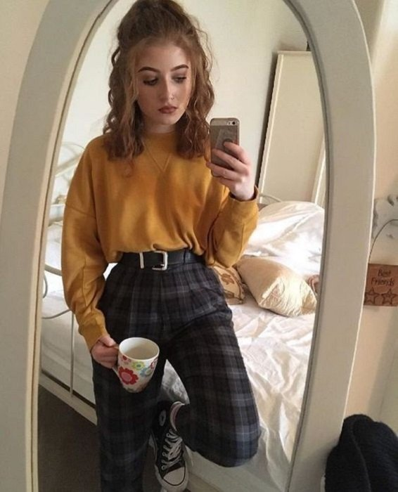 Girl wearing tartan print pants, black converse and mustard sweatshirt