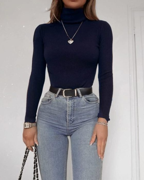 Girl wearing high-waisted denim jeans, with black belt and black long-sleeved high-neck blouse