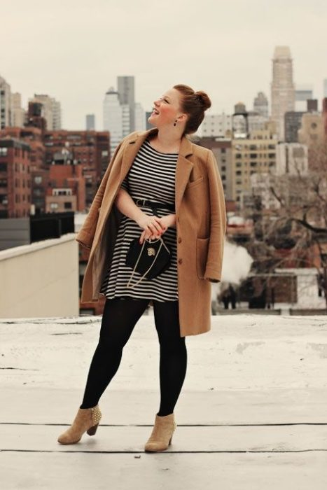 Curvy girl wearing camel ankle boots and jackets, with black stockings and bag and black and white striped dress