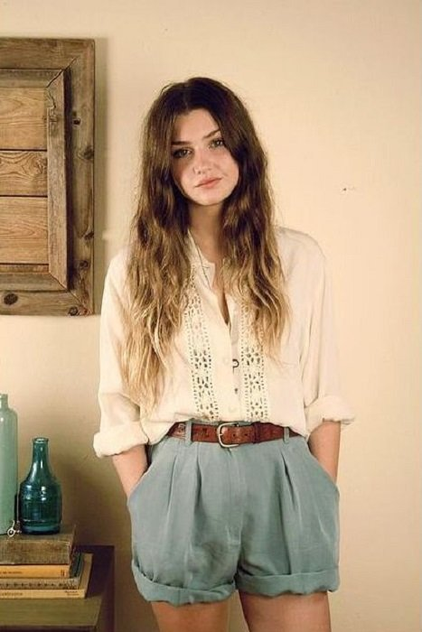 Girl wearing sky blue shorts, camel belt and loose white blouse