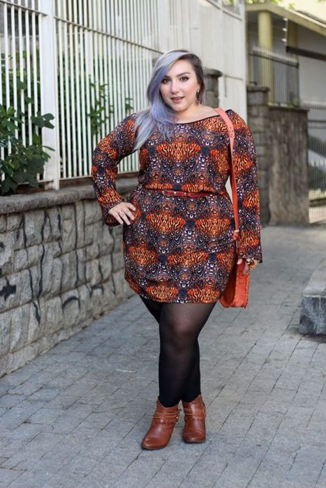 girl wearing bohemian print short long sleeve dress, black tights and camel ankle boots