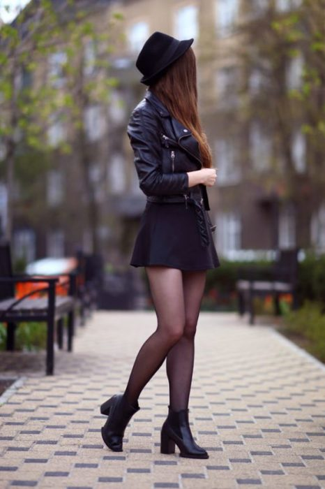 Girl wearing a total black look, with stockings, ankle boots, short dress, leather jacket and hat