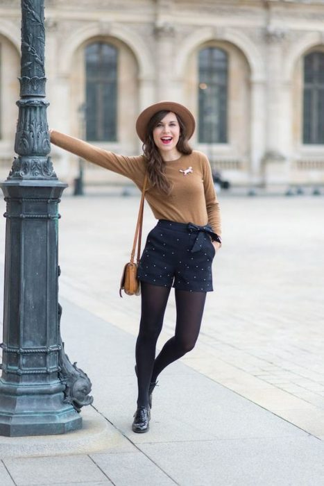 Girl wearing navy blue shot with black tights and booties, plus a sand-colored sweater and hat of the same color