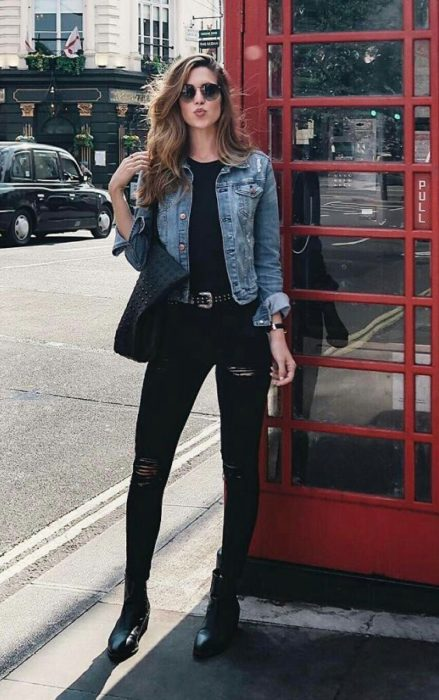 Girl wearing black blouse, jeans and ankle boots and a denim jacket