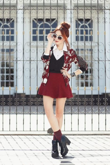 Girl wearing cherry A-line skirt, white shirt, black vest and cherry sweater with sand-colored details, cherry socks and black high-heeled ankle boots