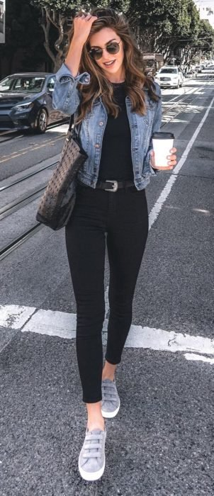 Girl wearing black leggings and blouse, denim jacket and gray tennis shoes