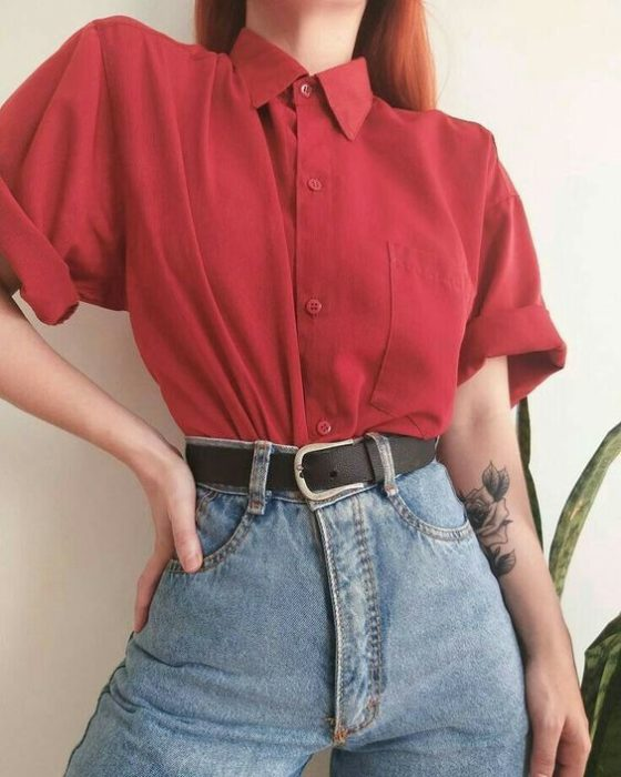 Girl wearing mom jeans, black belt and cherry red short sleeve shirt