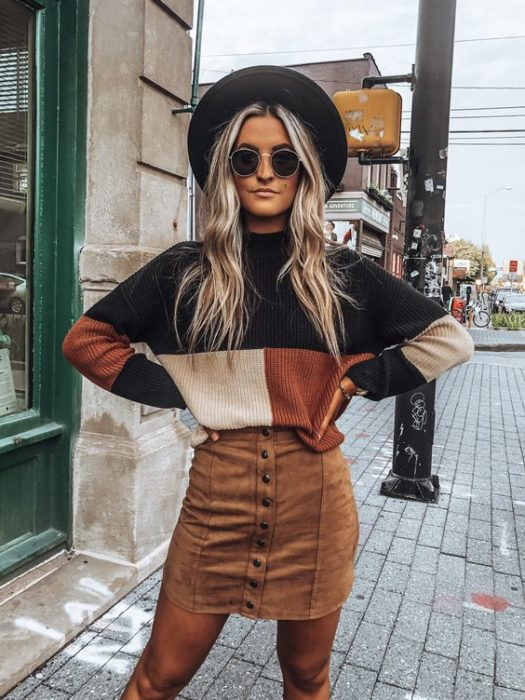 Girl wearing camel mini skirt, baggy sweater, black, beige and camel, black tights, sunglasses, and hat