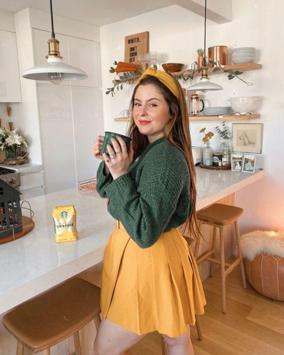 Curvy girl wearing mustard mini skirt and green sweater with mustard headband