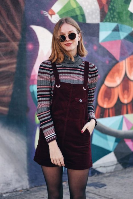 Corduroy outfit with a strapless dress with black tights and a striped print long-sleeved blouse and dark glasses